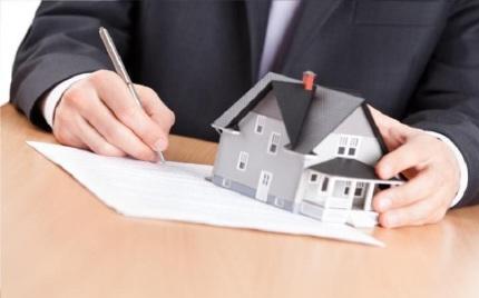 mesa-con-papeles-y-casa-encima-mano-firmando-papel